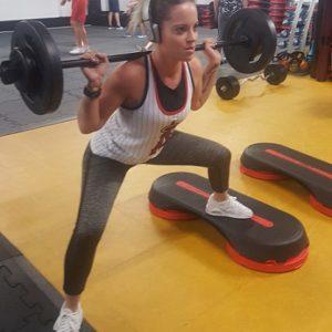 Notre adhérente effectue un squat avec barre et poids
